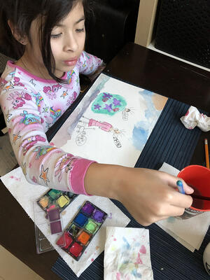 Sara uses watercolors to paint her drawings